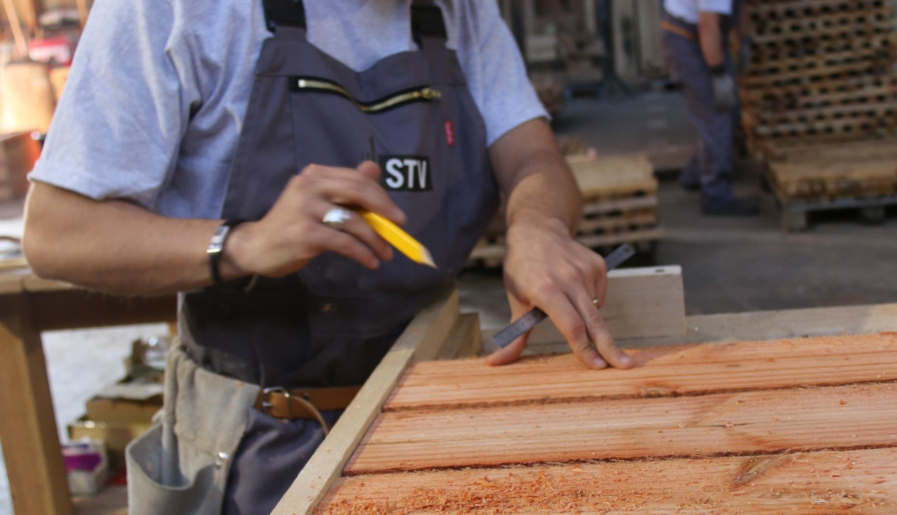 Menuisier travaillant avec une salopette au logo STV.